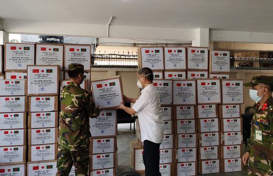 Wang Kun, China Railway Group limited (CREC)'s representative in Bangladesh, hands over donation of medical supplies to an official of a military-run hospital in Dhaka, Bangladesh on April 7, 2020. (Str/Xinhua)