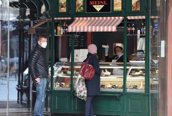 Customers visit a reopened snack bar at Graben street in Vienna, Austria on April 14, 2020. Some shops and businesses in Austria began to reopen from Tuesday. (Xinhua/Guo Chen)