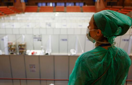A medical worker observes installation of beds for COVID-19 patients at a sports hall in Barcelona, Spain, April 13, 2020. (Vall d'Hebron Hospital/Handout via Xinhua)