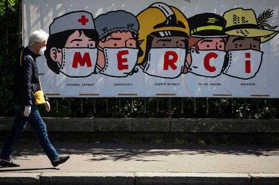 A resident walks past a poster thanking people in various professions during the epidemic in Paris, France, on April 14, 2020. (Photo by Aurelien Morissard/Xinhua)