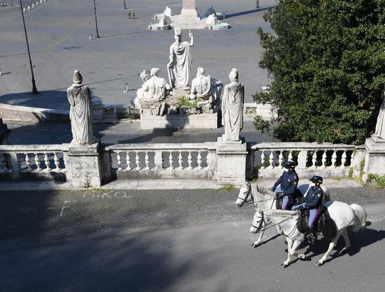 Two mounted police patrol in Rome, Italy, April 11, 2020. (Photo by Alberto Lingria/Xinhua)