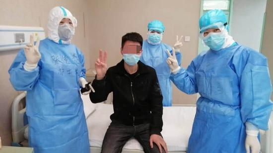A 21-year-old patient (in black) poses with his doctors at Ankang Hospital in the city of Mudanjiang, Heilongjiang Province. The man, who wants to remain anonymous, is the first imported case to have recovered amid the current outbreak at the China-Russia border.(Photo/CGTN)