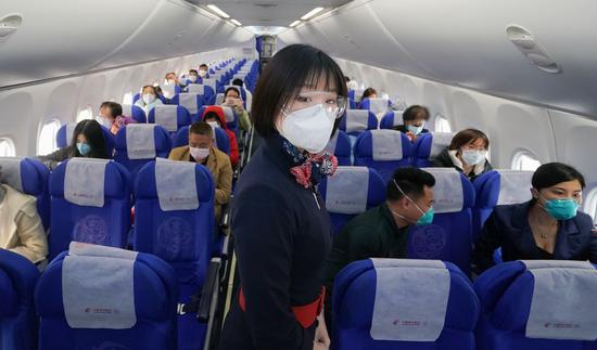 A flight attendant wearing a face mask and goggles serves passengers aboard flight MU2527 of China Eastern airlines at the Tianhe International Airport in Wuhan, central China's Hubei Province, April 8, 2020. (Xinhua/Cheng Min)