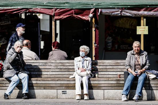 People rest on a bench with social distancing in Berlin, capital of Germany, April 11, 2020. (Photo by Binh Truong/Xinhua)