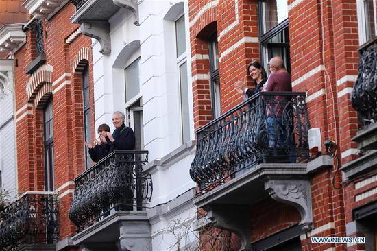 人们在阳台上鼓掌,以表示对布鲁塞尔前线工作人员的尊重