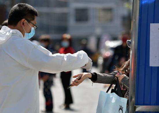 2020年4月15日,一名工作人员在中国中部湖北省武汉市武汉市武昌区楚才社区入口处检查居民的体温。(新华网/李鹤)