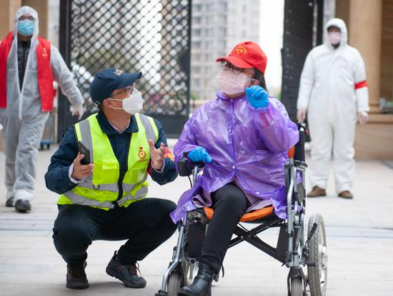 Du Chengcheng (in wheelchair) communicates with a volunteer as they deliver supplies to households at Jiangjiadun community in Wuhan, Hubei province, on March 1. (PHOTO/CHINA DAILY)