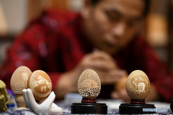 Craftman makes egg carving works at intangible cultural heritage base