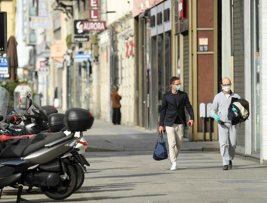 People wearing face masks walk on a street in Milan, Italy, on April 18, 2020. (Xinhua)