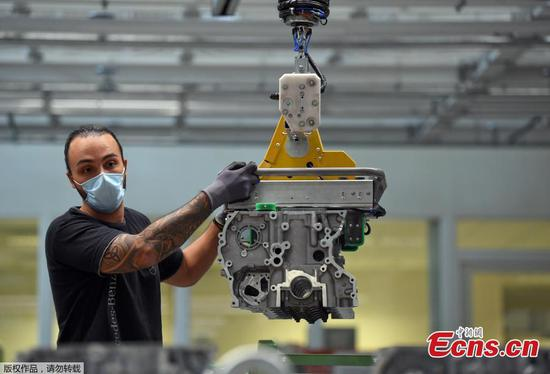 With masks and distancing, auto company restarts production