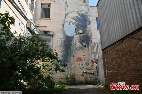 Banksy's 'Girl with a Pierced Eardrum' gains a coronavirus face mask