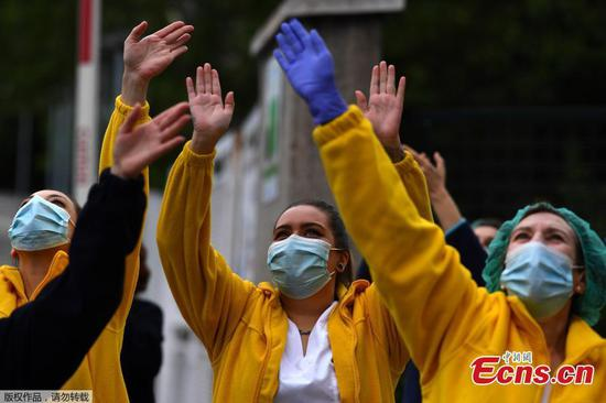Healthcare workers applaud to cheer people in quarantine