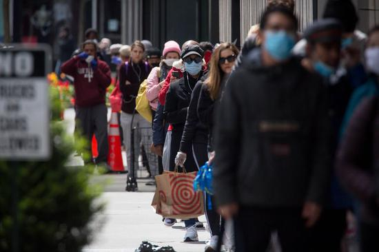 People wearing face masks wait in line to do shopping at a store during the coronavirus pandemic in the Brooklyn borough of New York, the United States, on April 14, 2020. (Photo by Michael Nagle/Xinhua)