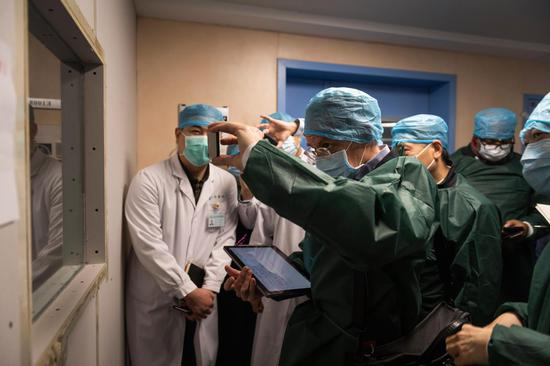Members of the China-WHO joint novel coronavirus epidemic inspection team visit the Wuhan Tongji Hospital's Guanggu branch in Wuhan on Feb 23.(Photo by Pan Songgang/For China Daily)