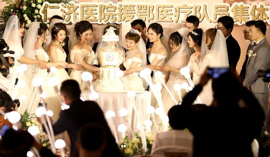 A mass wedding is held for medical workers from Renji Hospital at the Waldorf Astoria Shanghai on the Bund on Friday. The workers postponed their scheduled weddings to join the fight against COVID-19 in Wuhan, Hubei province. [Photo/China Daily]