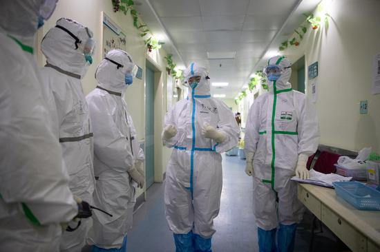 Zhang Jixian (2nd R), director of the respiratory and critical care medicine department of Hubei Provincial Hospital of Integrated Chinese and Western Medicine, communicates with her colleagues at the hospital in Wuhan, central China's Hubei Province, March 11, 2020. (Photo by Ke Hao/Xinhua)