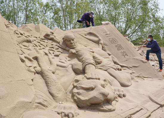 Sand sculpture world prepares for opening in north China's seaside resort