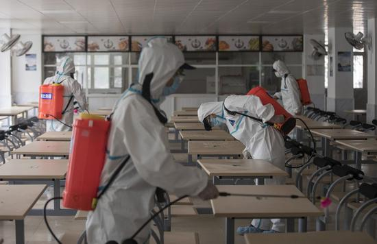 Firefighters disinfect the canteen in Wuhan No. 23 Middle School in Wuhan, central China's Hubei Province, April 22, 2020. (Xinhua/Fei Maohua)