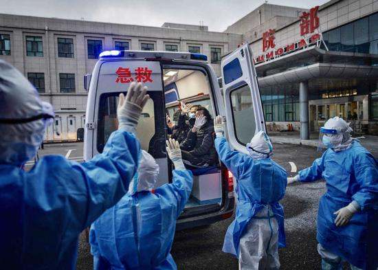 Members of the first group of imported COVID-19 patients diagnosed at Suifenhe port in Northeast China's Heilongjiang province who were cured and discharged from the hospital on April 21, 2020 wave goodbye to medics. (Photo by Pan Songgang/For chinadaily.com.cn)