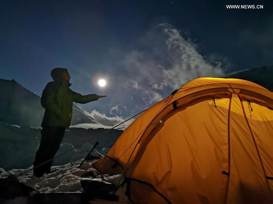 图为满月在中国西南部西藏的珠穆朗玛峰山预先营地