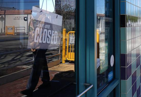 A pedestrian wearing a face mask walks past a closed shop in San Mateo City, California, the United States, April 2, 2020. (Xinhua/Wu Xiaoling)