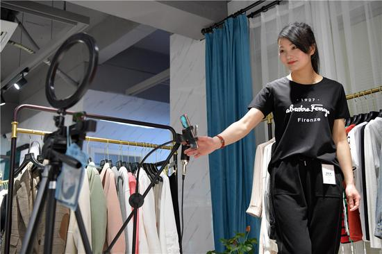 A model promotes clothes online in Nanchang, East China's Jiangxi province, on March 25, 2020. (Photo/Xinhua)