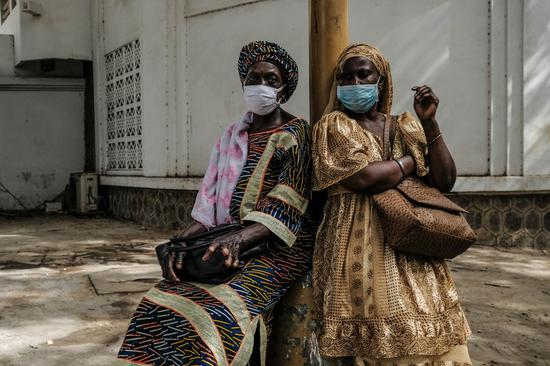 Women wearing face masks wait for a taxi in Dakar, Senegal, May 12, 2020. (Photo by Eddy Peters/Xinhua)