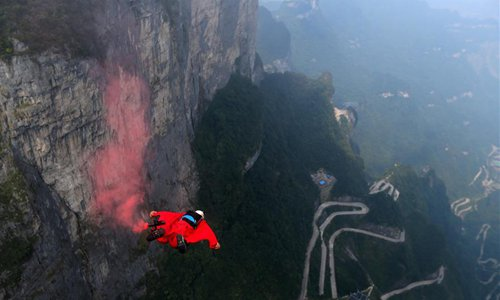 A wingsuit flyer glides through the air during a wingsuit flying competition held at the Tianmen Mountain scenic spot in Zhangjiajie, central China's Hunan Province, Sept. 14, 2018. (Xinhua/Zhou Guoqiang)