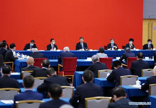 Chinese President Xi Jinping, also general secretary of the Communist Party of China (CPC) Central Committee and chairman of the Central Military Commission, visits national political advisors from the economic sector attending a joint panel discussion at the third session of the 13th National Committee of the Chinese People's Political Consultative Conference (CPPCC) in Beijing, capital of China, May 23, 2020. Xi joined them in the discussion and heard their comments and suggestions. Wang Yang, a member of the Standing Committee of the Political Bureau of the CPC Central Committee and chairman of the CPPCC National Committee, also attended the discussion. (Xinhua/Xie Huanchi)