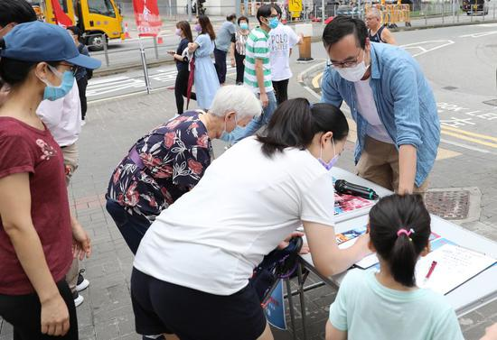 Citizens write down their signatures in a street campaign in support of the national security legislation in Hong Kong, south China, May 22, 2020. (Xinhua/Wu Xiaochu)