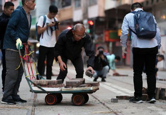 Local residents clear roadblocks on a street in Sai Wan Ho of Hong Kong, south China, Nov. 15, 2019. (Xinhua)