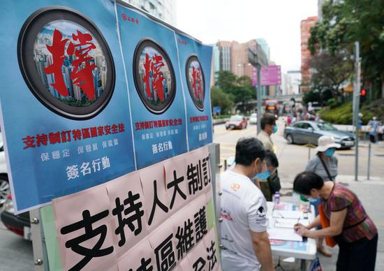 A resident signs in a street campaign in support of national security legislation for Hong Kong Special Administrative Region in Hong Kong, China, May 23, 2020. (Xinhua/Li Gang)