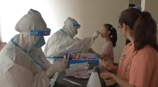 Residents in Wuhan take swabs from a mother and her daughter during a 10-day campaign, May 13, 2020. (CCTV)