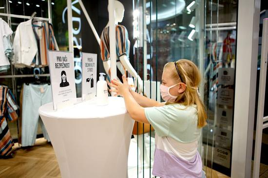 A girl washes her hands with sanitizer gel at a shop in Prague, the Czech Republic, on May 11, 2020. (Photo by Dana Kesnerova/Xinhua)