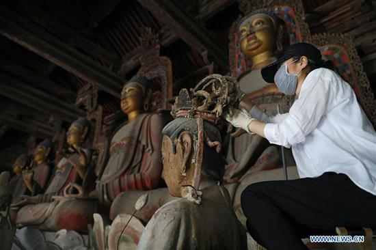 Relic conservation experts restore colour-painted clay sculptures at Fengguo Monastery in Liaoning