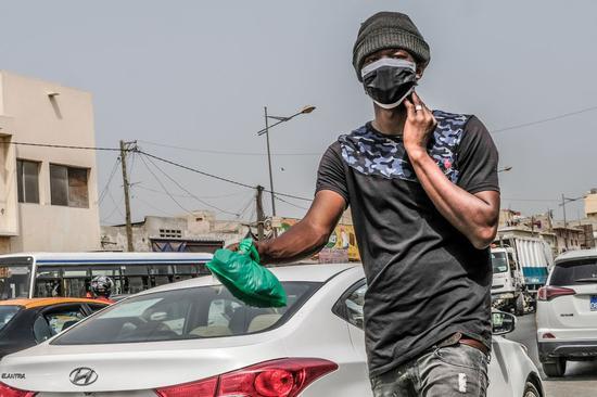 2020年6月3日,一名戴着口罩的男子在塞内加尔达喀尔的街道上行走。(新华社/埃迪·彼得斯)