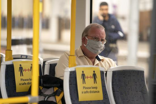 A man wearing a face mask sits in a tram at Manchester Victoria Railway Station in Manchester, Britain, on June 15, 2020. (Photo by Jon Super/Xinhua)