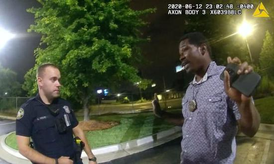 This screengrab taken from body camera video shows Garrett Rolfe (L), then the Atlanta police officer, listening to the 27-year-old African American Rayshard Brooks in the moments before Brooks' killing on June 12, 2020 in the U.S. city of Atlanta in Georgia State. (Photo credit: Atlanta Police Department)