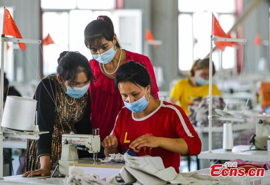 People work at factory in relocation area in Xinjiang