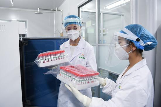 Staff members hold inactivated samples for nucleic acid test at the laboratory of KingMed Diagnostics, a Chinese medical diagnostic testing company in Beijing, capital of China, June 25, 2020. (Xinhua/Ju Huanzong)