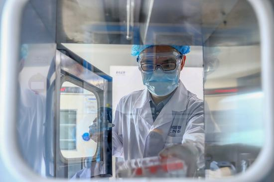 A staff member takes out samples of the COVID-19 inactivated vaccine at a vaccine production plant of Sinopharm in Beijing, on April 11, 2020. (Photo/Xinhua)