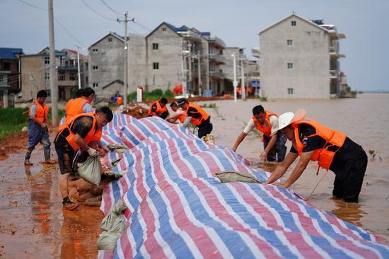 救援人员于2020年7月11日在水果机东部江西省Po阳县的姜家岭村村修建了临时的防水堤防洪水。(新华社/张浩波)