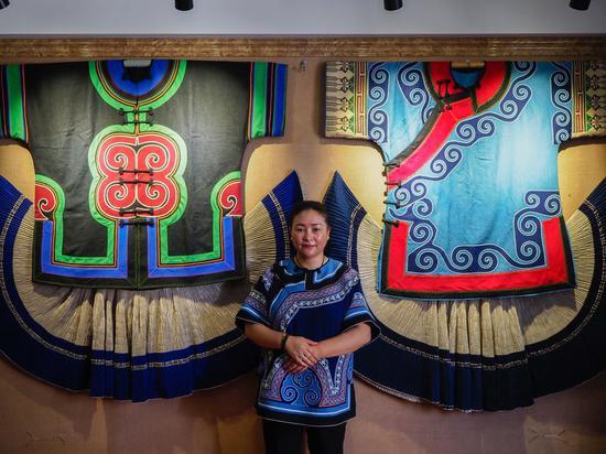 申小英和她制作的彝族服饰,2020年6月17日。(新华社/王迪)