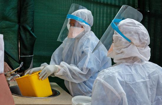 Staff wearing protective suits clean garbage at a hospital in Pretoria, South Africa, July 10, 2020.(Xinhua/Yeshiel)