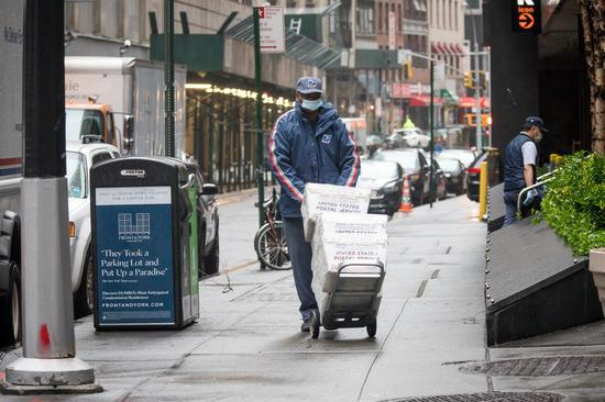 A United States Postal Service (USPS) worker wearing a mask delivers mails during the COVID-19 pandemic in New York, the United States, April 13, 2020. (Photo by Michael Nagle/Xinhua)