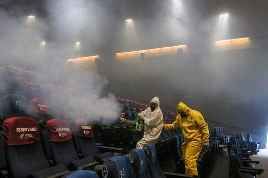 Workers sanitize a hall of a movie theater in Mexico City, Mexico, Aug. 12, 2020. Some movie theaters in Mexico City have reopened to the public with epidemic prevention measures in place. (Photo by Israel Rosas/Xinhua)