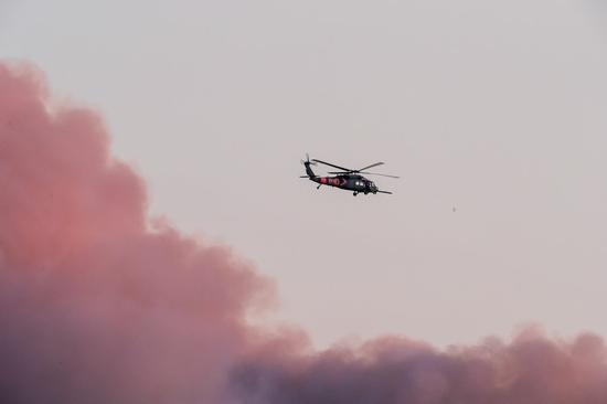 Photo taken on Aug. 19, 2020 at the Windy Hill Open Space Preserve of San Mateo County shows a helicopter flying over the dense smoke of wildfires in San Francisco Bay Area, California, the United States. (Photo by Dong Xudong/Xinhua)