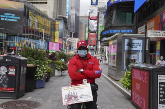 A tour bus ticket salesperson waits for customers on Times Square in New York, the United States, Aug. 31, 2020. (Xinhua/Wang Ying)