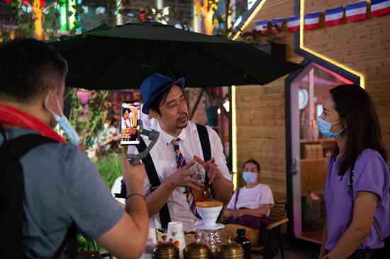 A coffee shop staff member (C) attends a livestreamed interview during a shopping carnival held in the Wangjing subdistrict as part of a consumption stimulus plan in Chaoyang District, Beijing, capital of China, Aug. 8, 2020. (Xinhua/Chen Zhonghao)