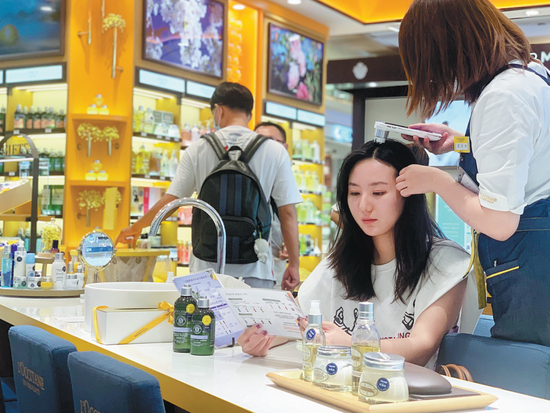 A customer experiences haircare service at a L'Occitane store in Shanghai in September. CHINA DAILY